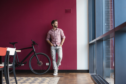 Man with bicycle standing in modern office looking out of window